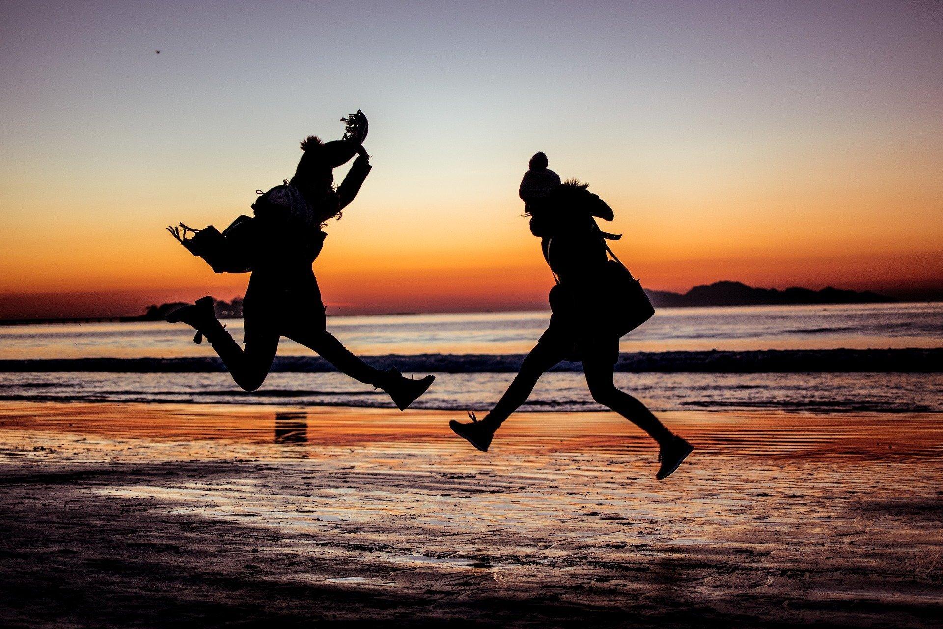 amiche al tramonto in riva al mare che saltano e giocano tra di loro
