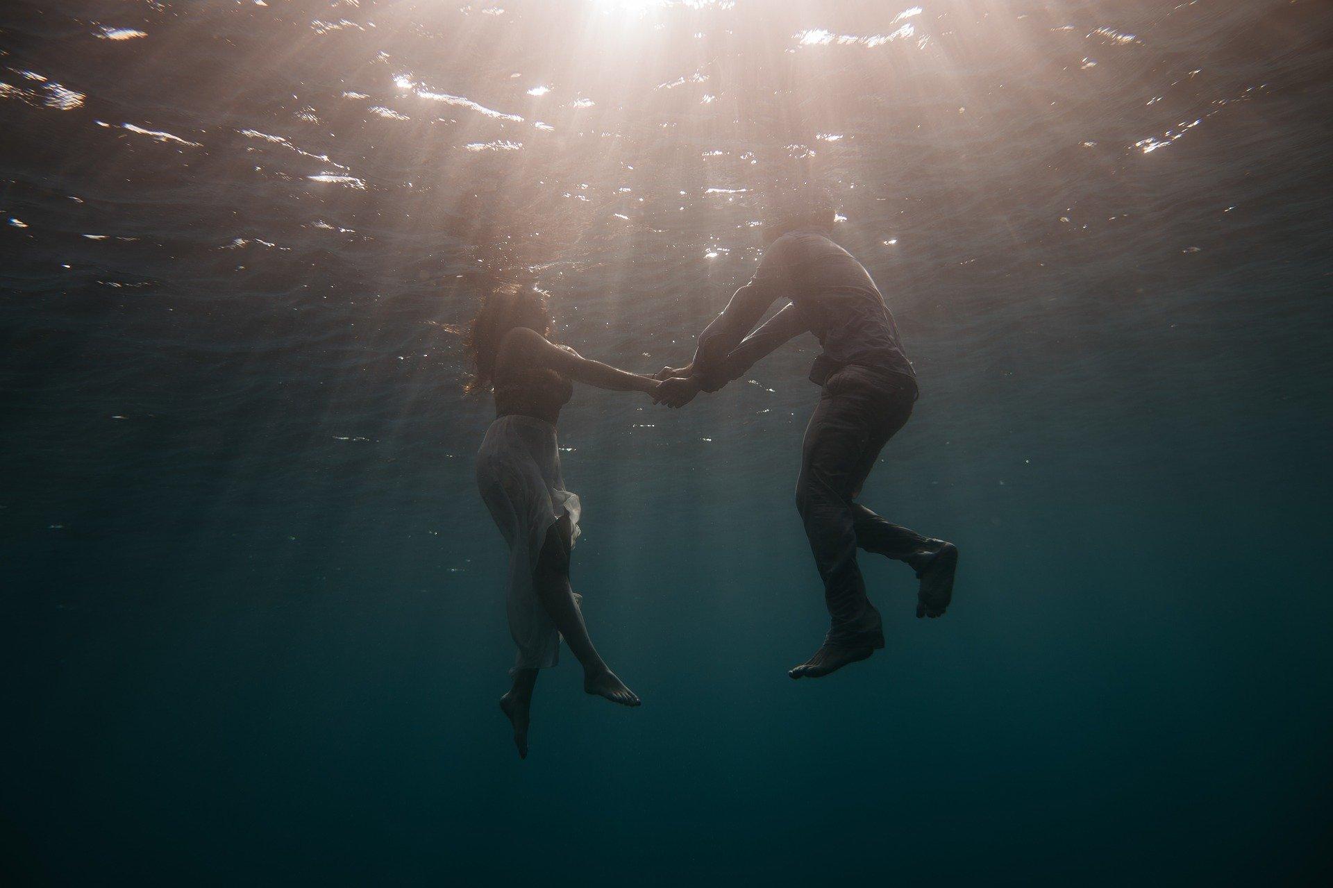 un uomo e una donna fotogeafati da sott'acqua che si tengono per mano restando a galla