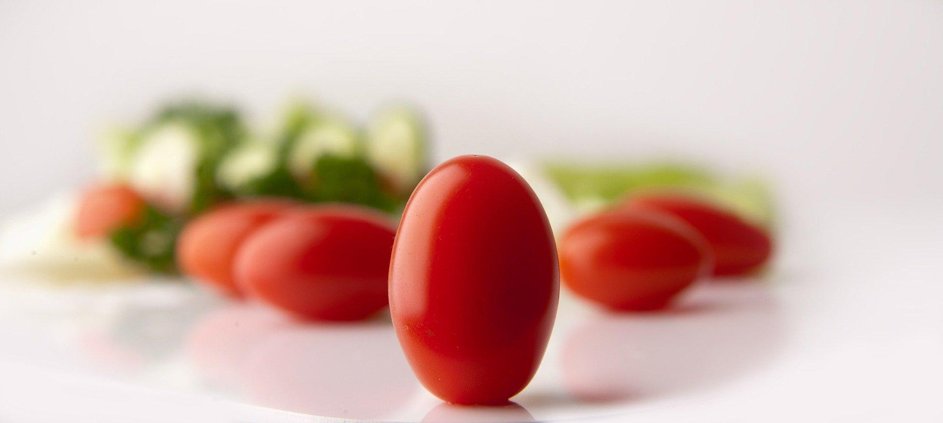 pomodori su un tavolo bianco di cui uno in primo piano