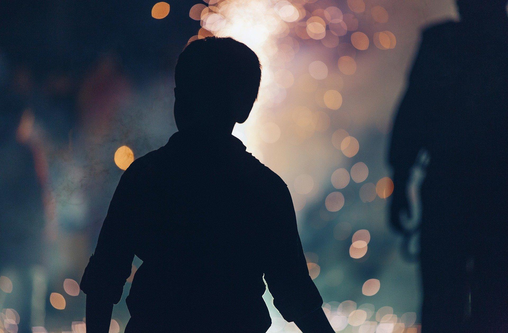 ombra di un bambino di spalle e davanti le luci dei fuochi d'artificio