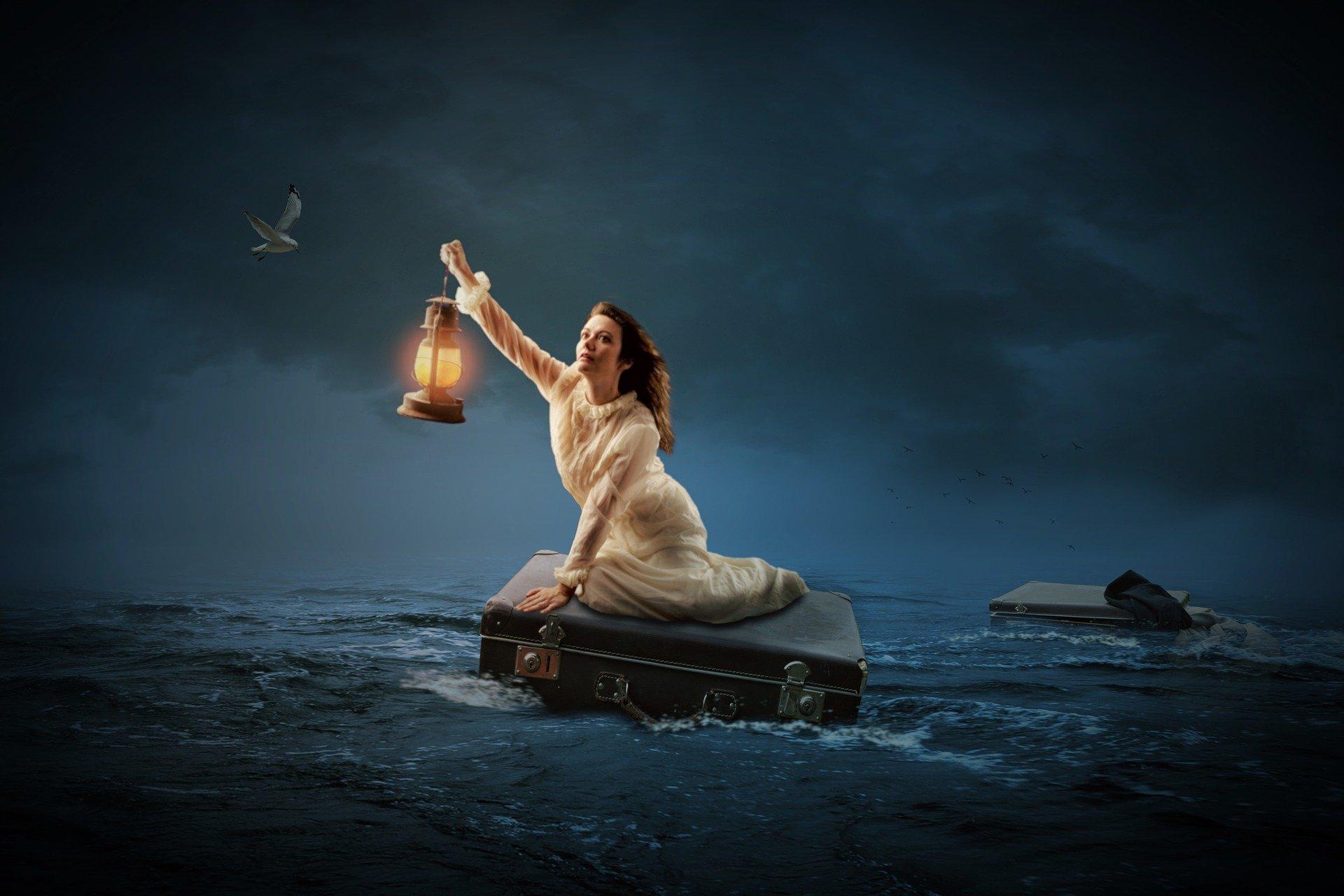 una donna in mezzo al mare seduta su una valigia mentre si fa luce con una lanterna