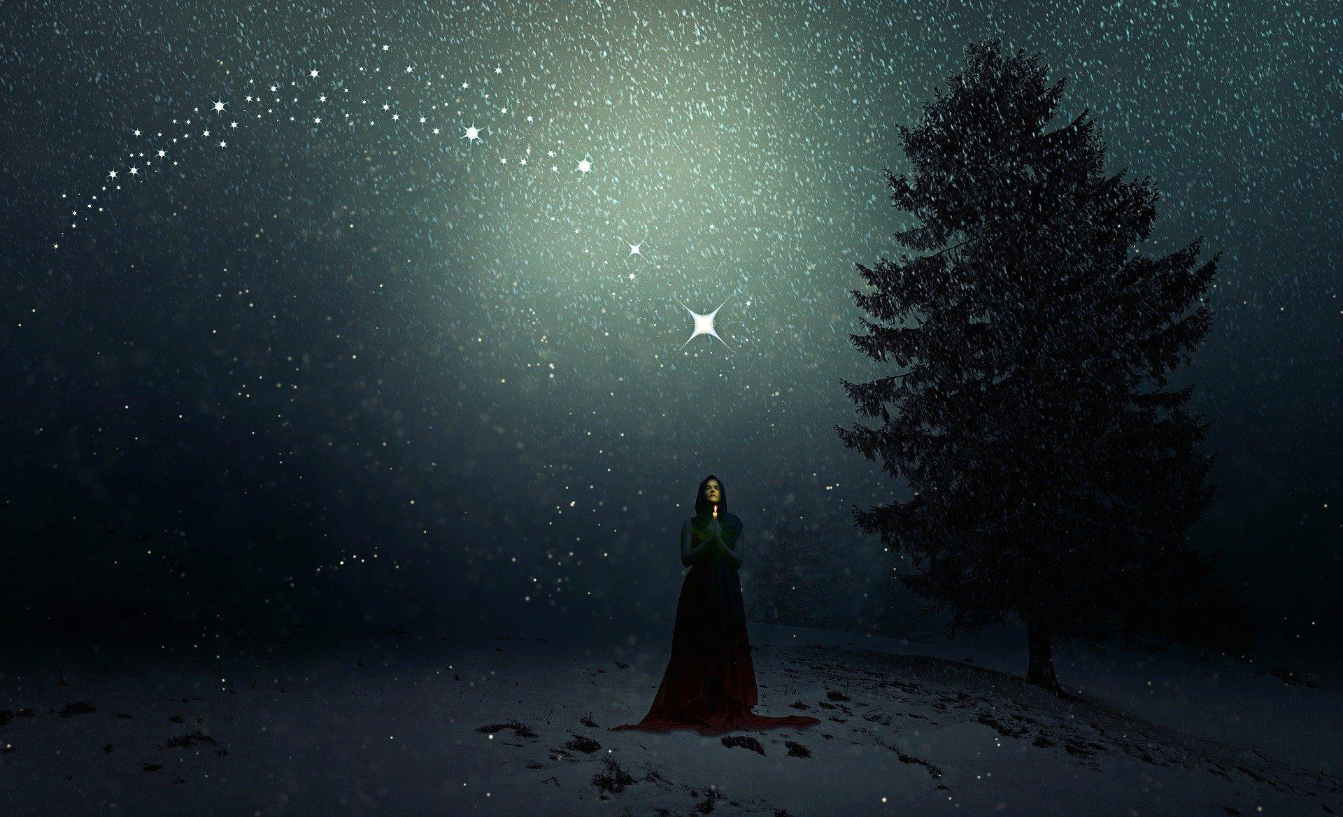 donna di notte con mantella lunga che tiene in mano una piccola luce mentre si rivolge alle stelle lucenti in cielo