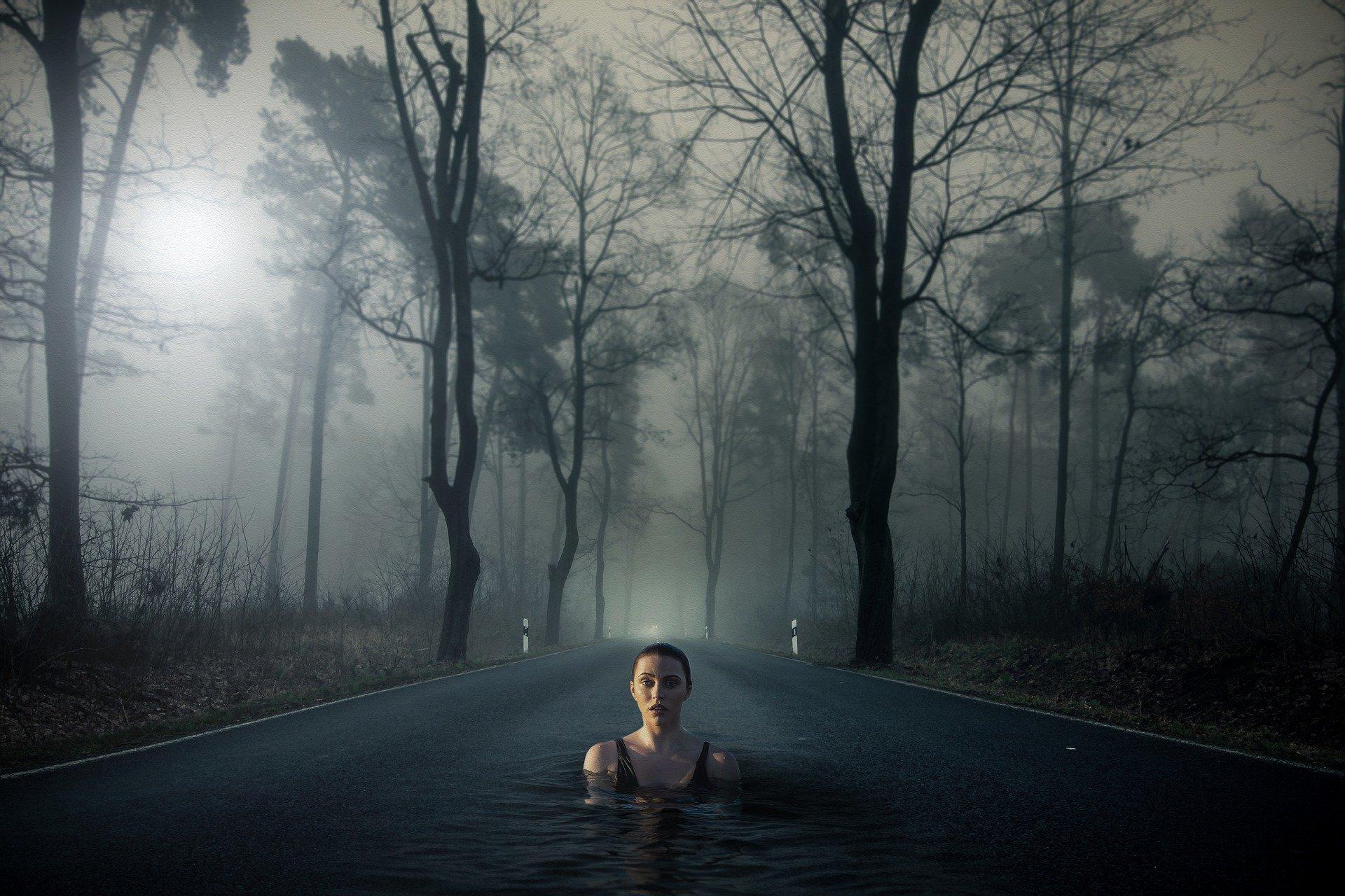 una donna immersa nell'acqua di una strada in mezzo ad alberi e nebbia