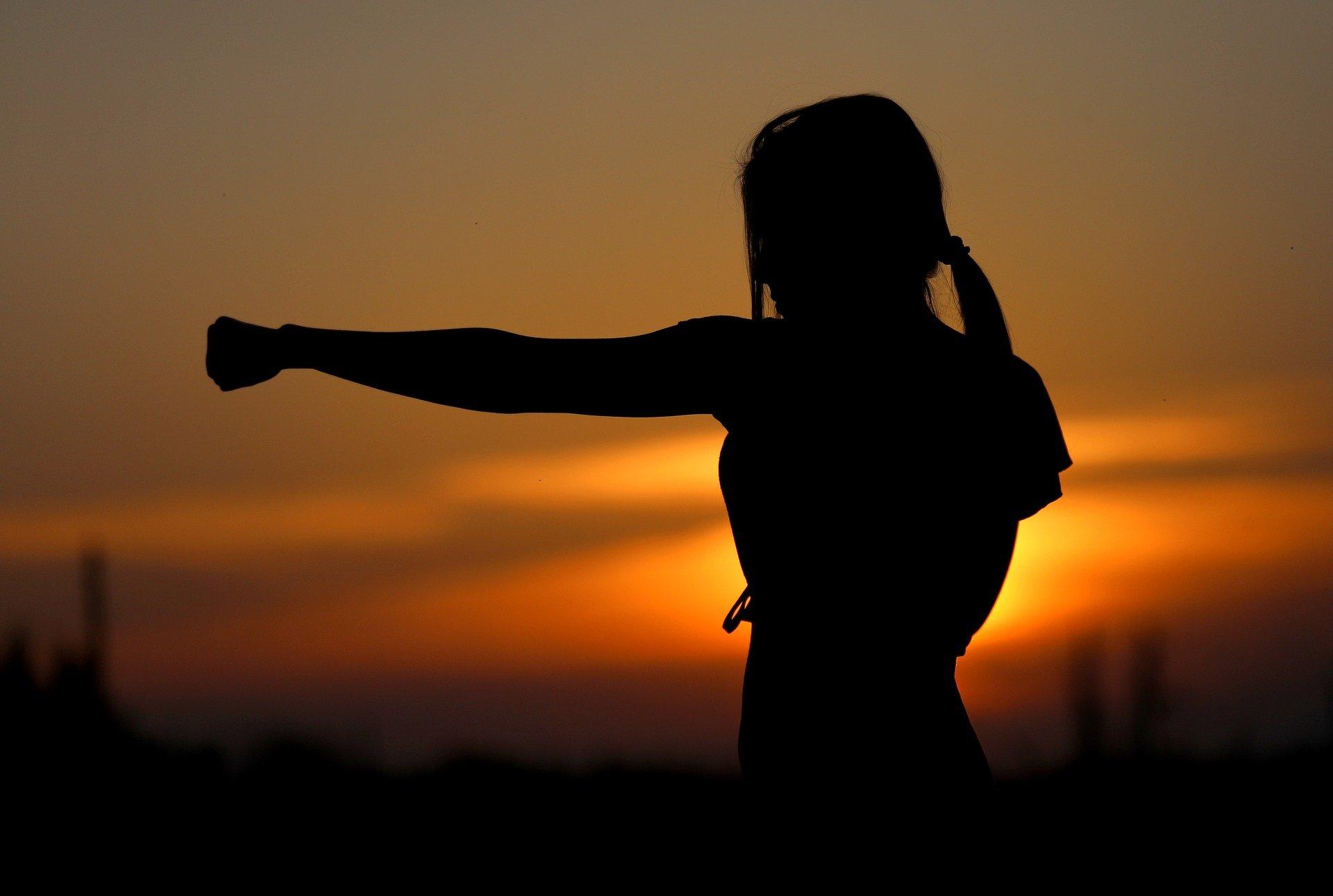 sagoma di una donna al tramonto che si allena a tirare pugni