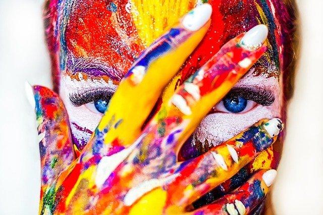 Viso e mani sono cosparsi di vernici colorate
