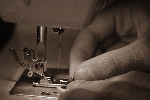 Una mano regola i dettagli prima di avviare una macchina da cucire