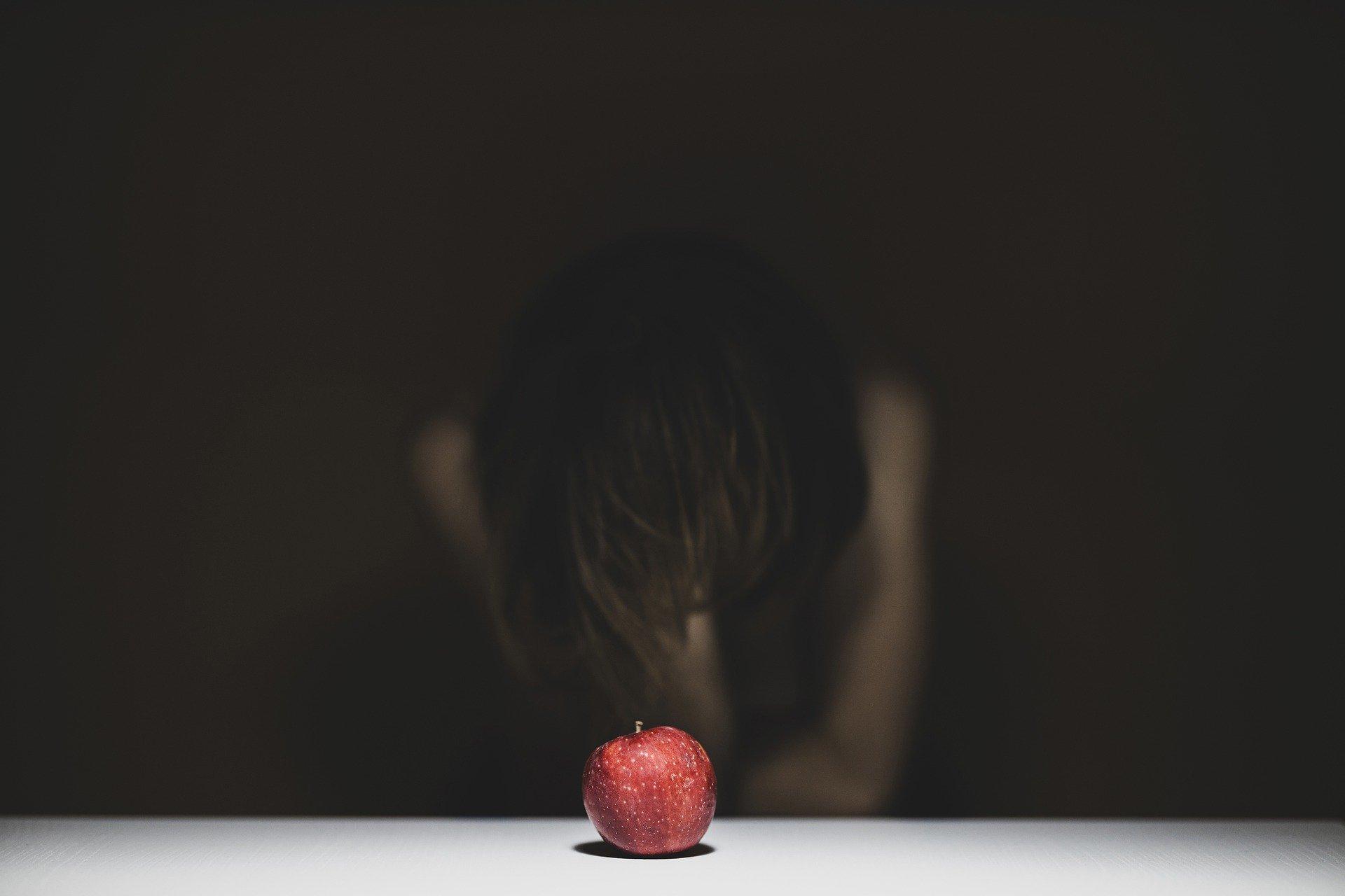 una donna china su se stessa con la testa tra le mani e davanti a sè una mela rossa sopra un tavolo