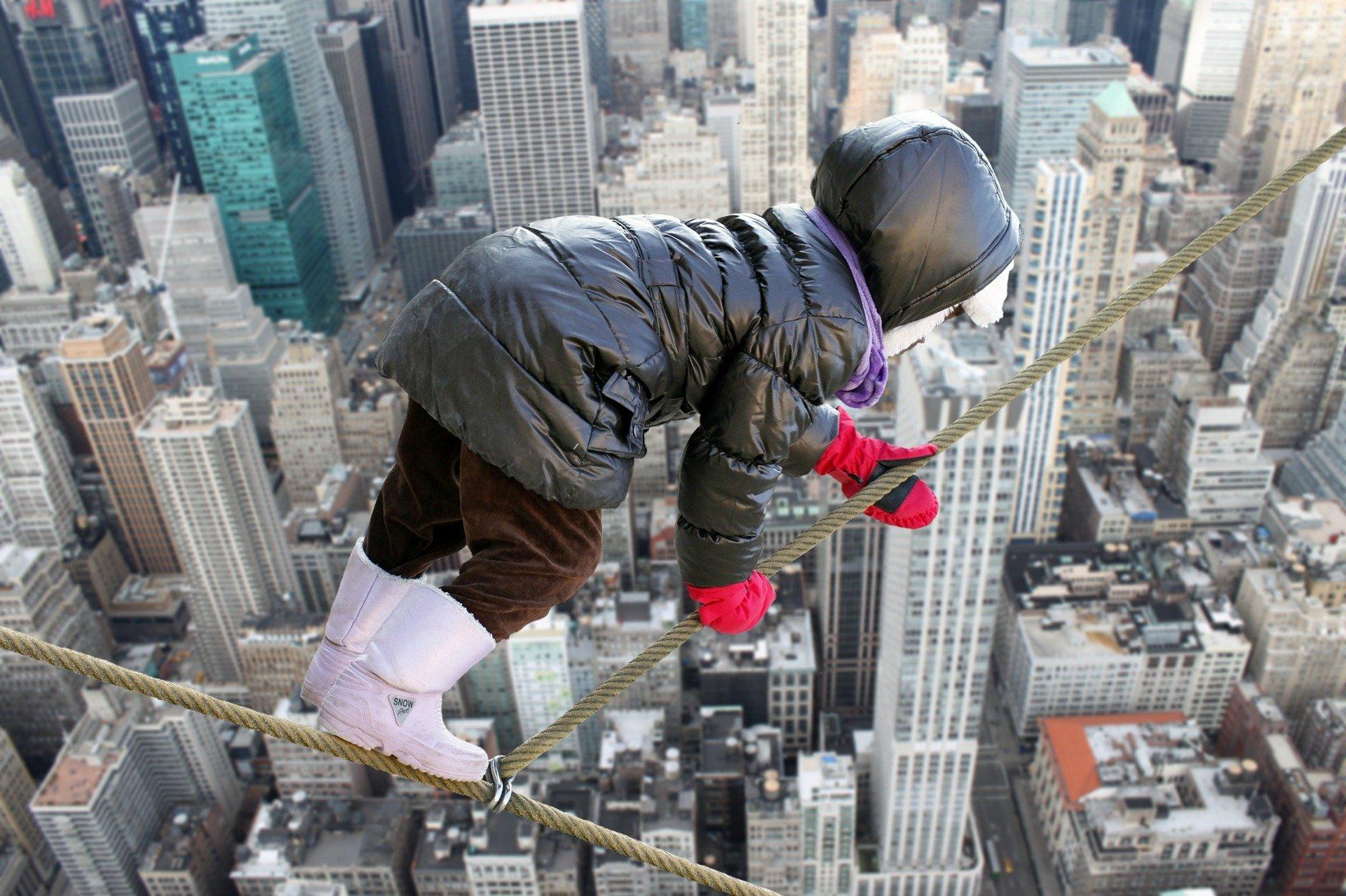 un bambino sospeso sopra i grattacieli della città che si tiene su una corda
