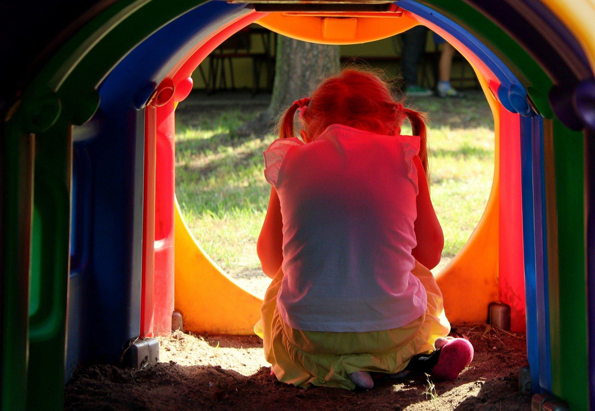 una bambina di spalle seduta dentro uno scivolo chiuso
