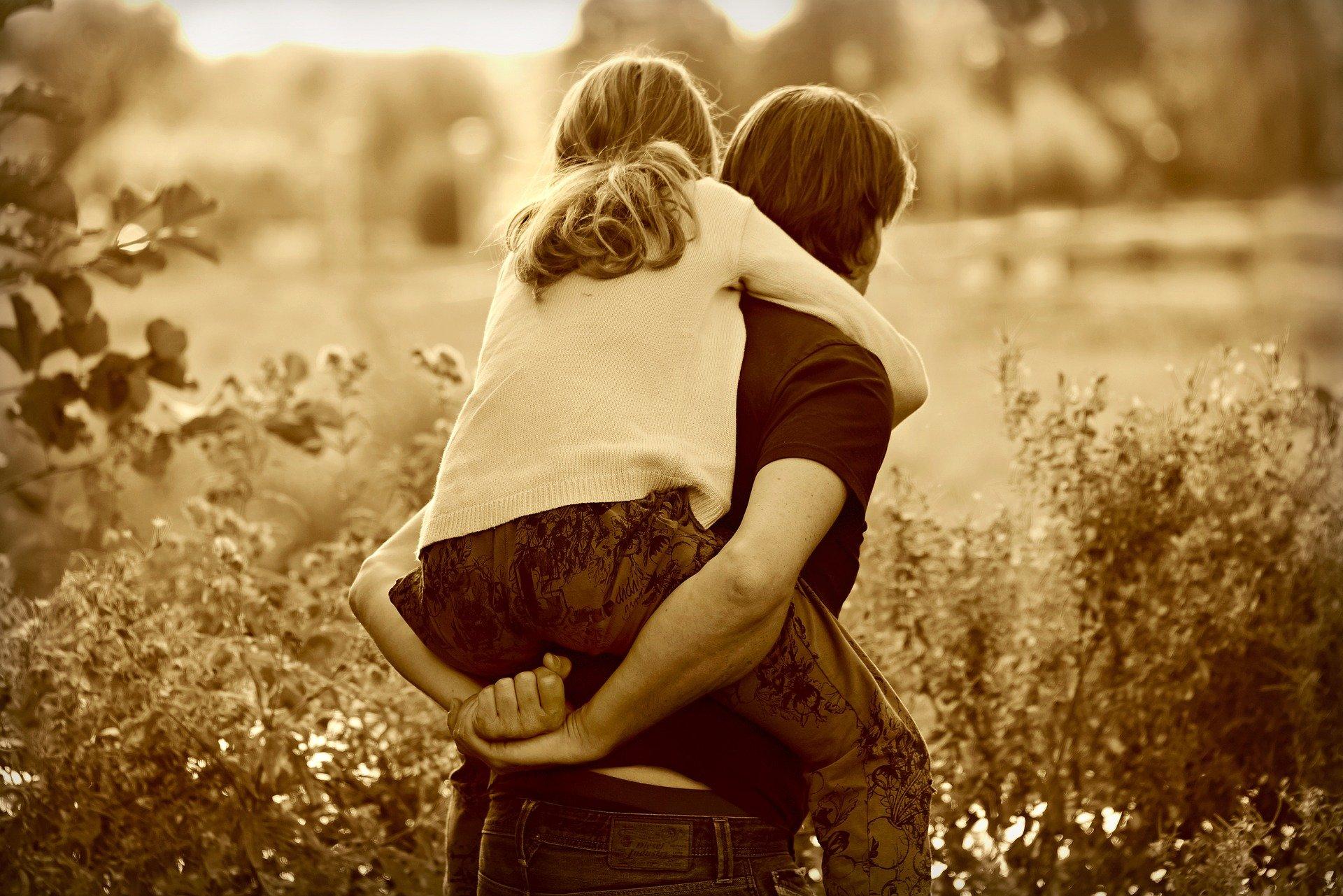 un uomo di spalle in un campo che tiene sulle spalle una bambina