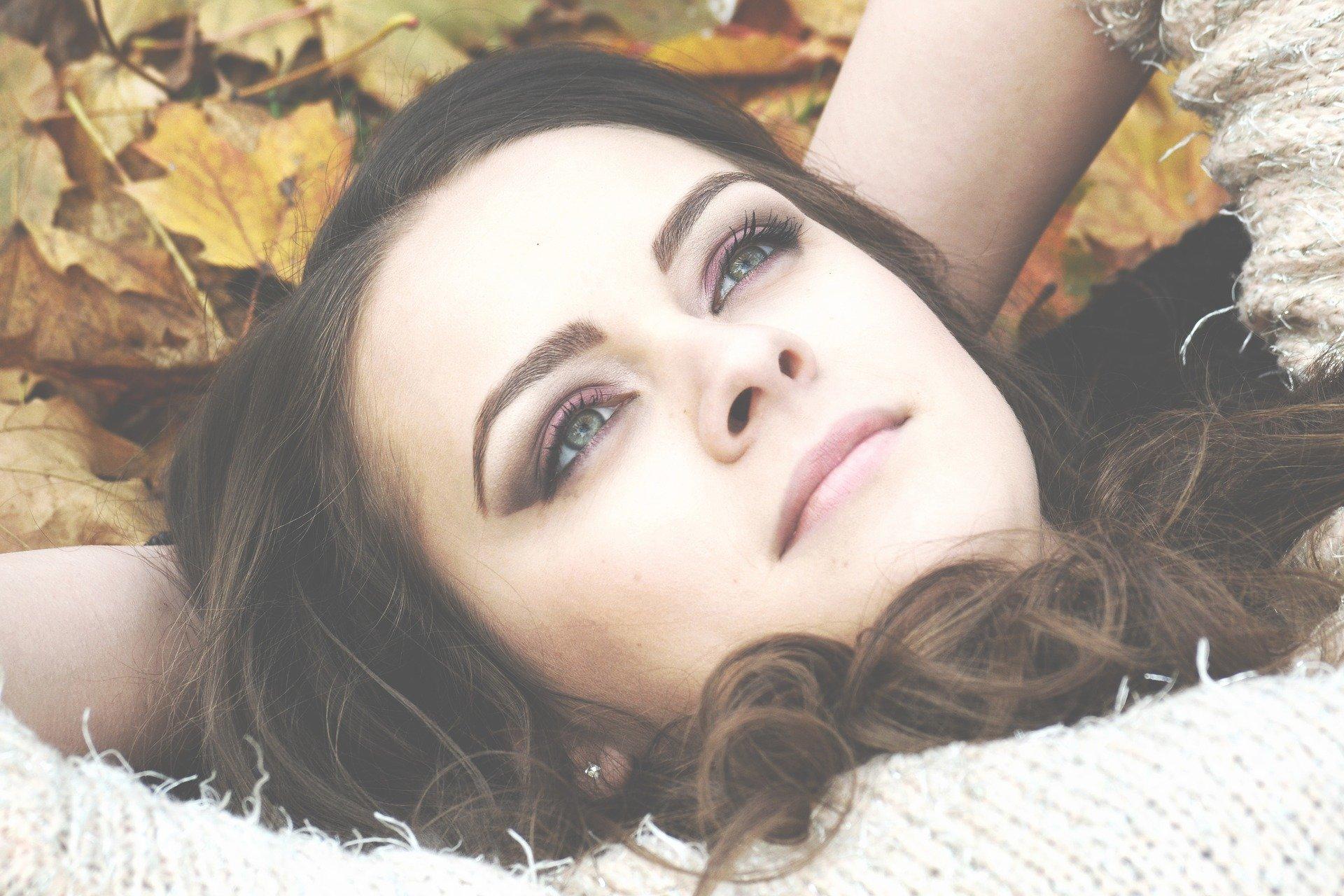 volto di una donna sdraiata a terra tra le foglie autunnali
