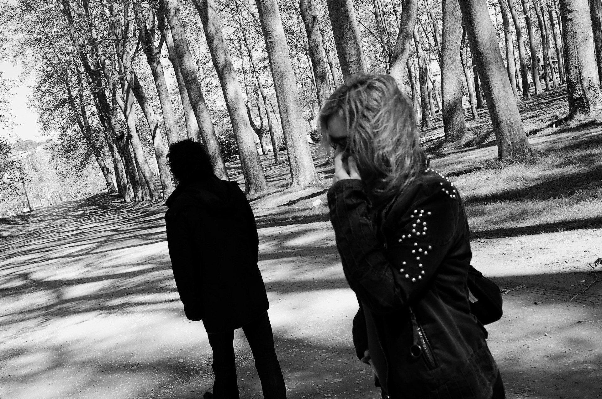 un uomo ed una donna che si allontanano tra di loro in mezzo ad un bosco