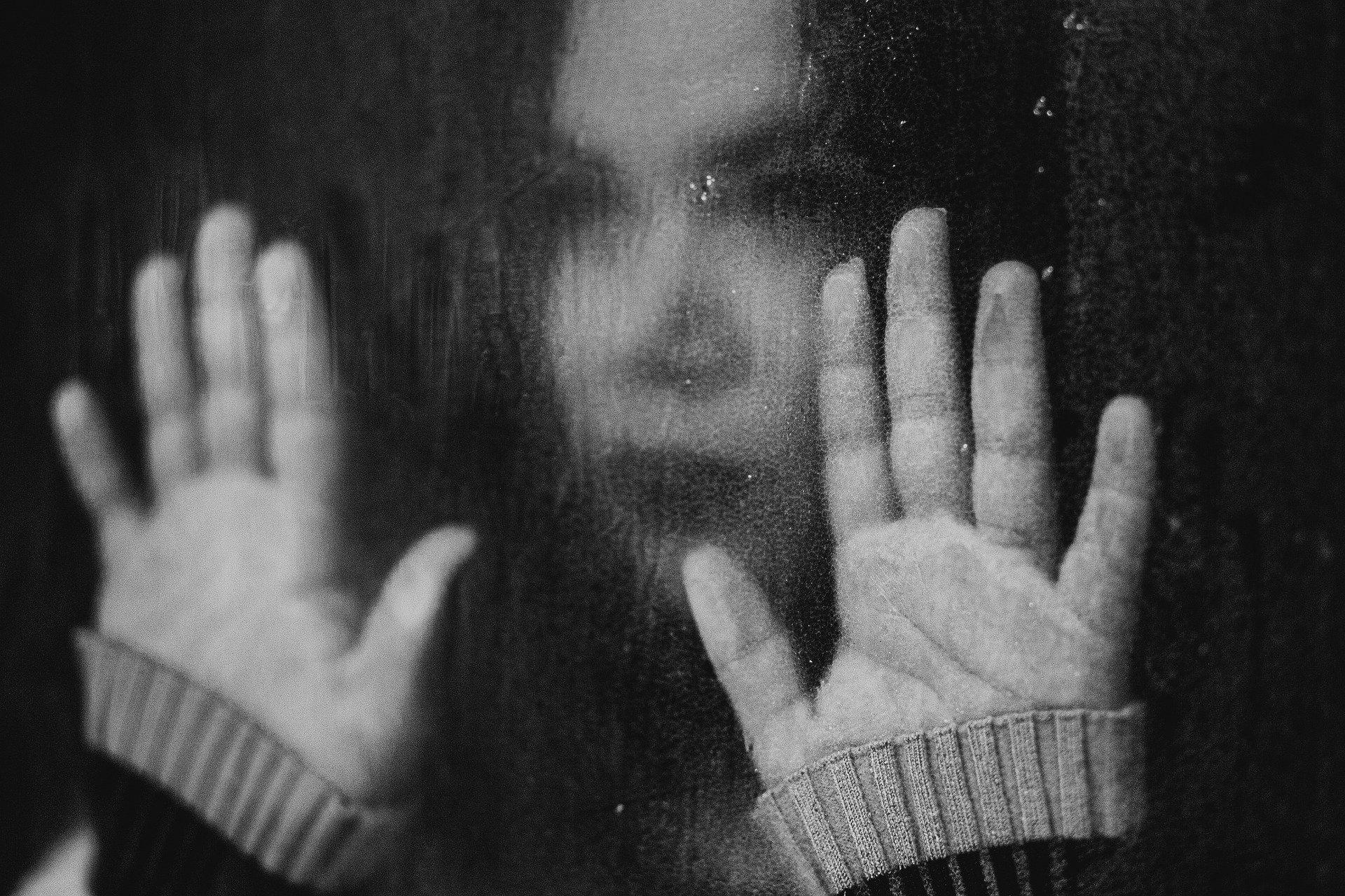 volto di una donna appoggiata con le mani ad un vetro