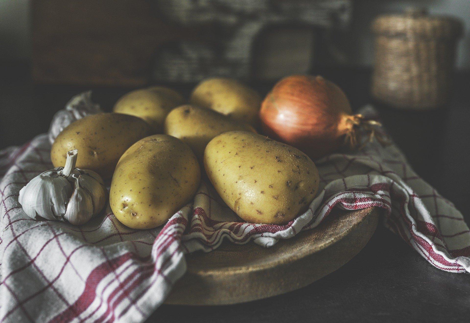 su un tagliere coperto da un canovaccio, patate e cipolle