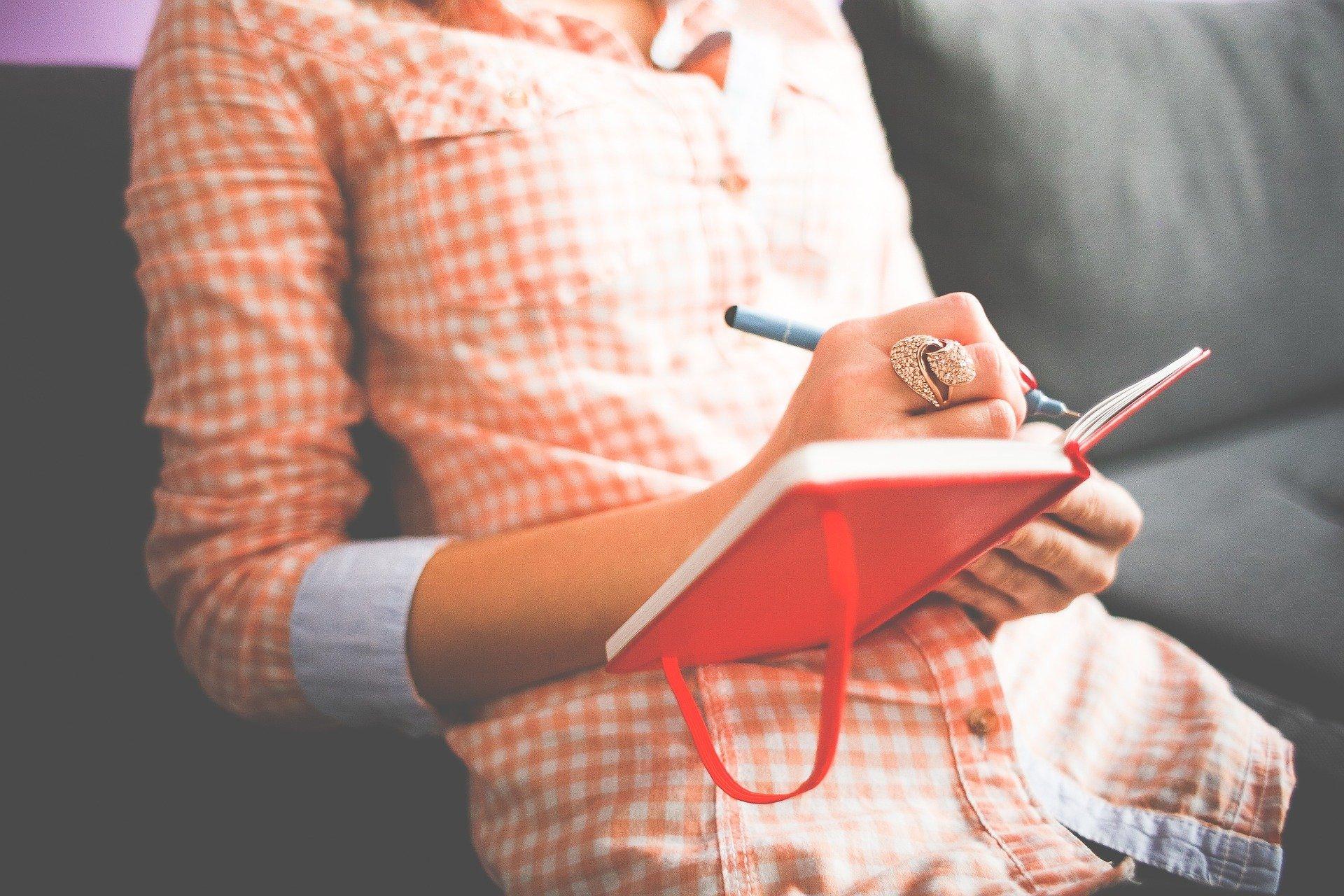 busto di donna seduta mentre scrive in un'agenda