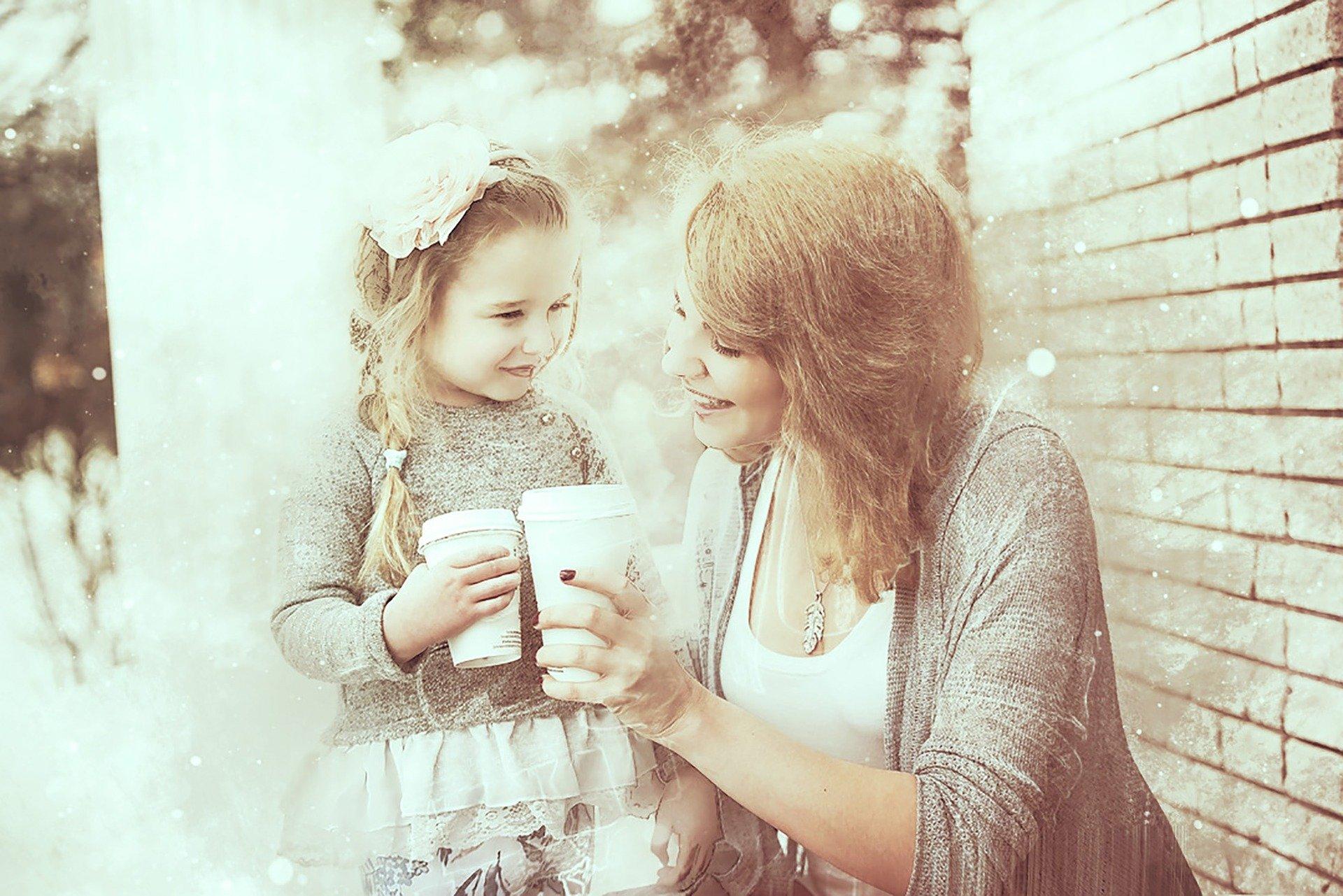 ritratto di madre e figlia che brindano con una bevanda da asporto