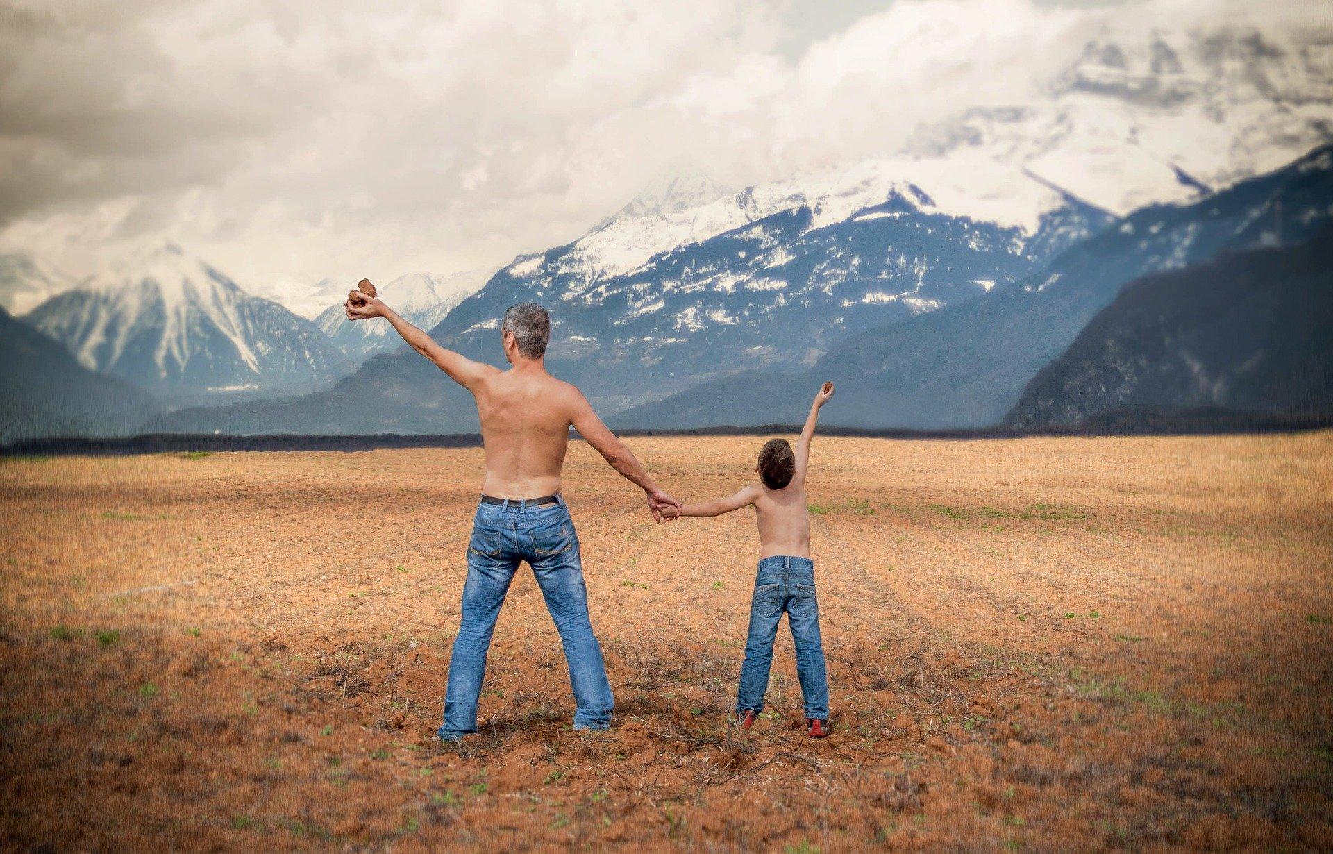 su un campo in montagna, padre e figlio a dorso nudo che si tengono per mano e con l'altra alzata in cielo tenendo un oggetto