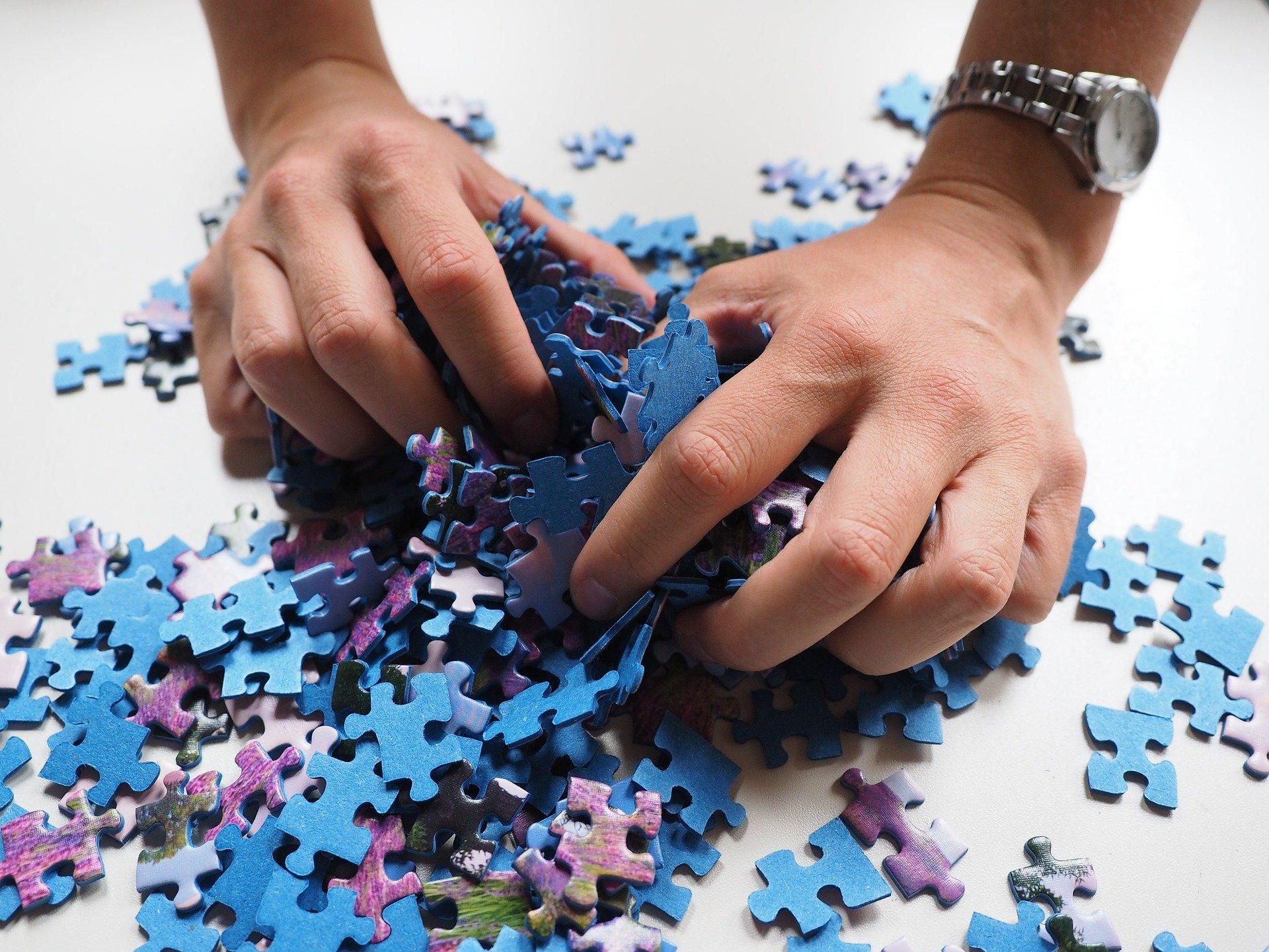 mani di un uomo tra tanti pezzi di puzzle alla rinfusa