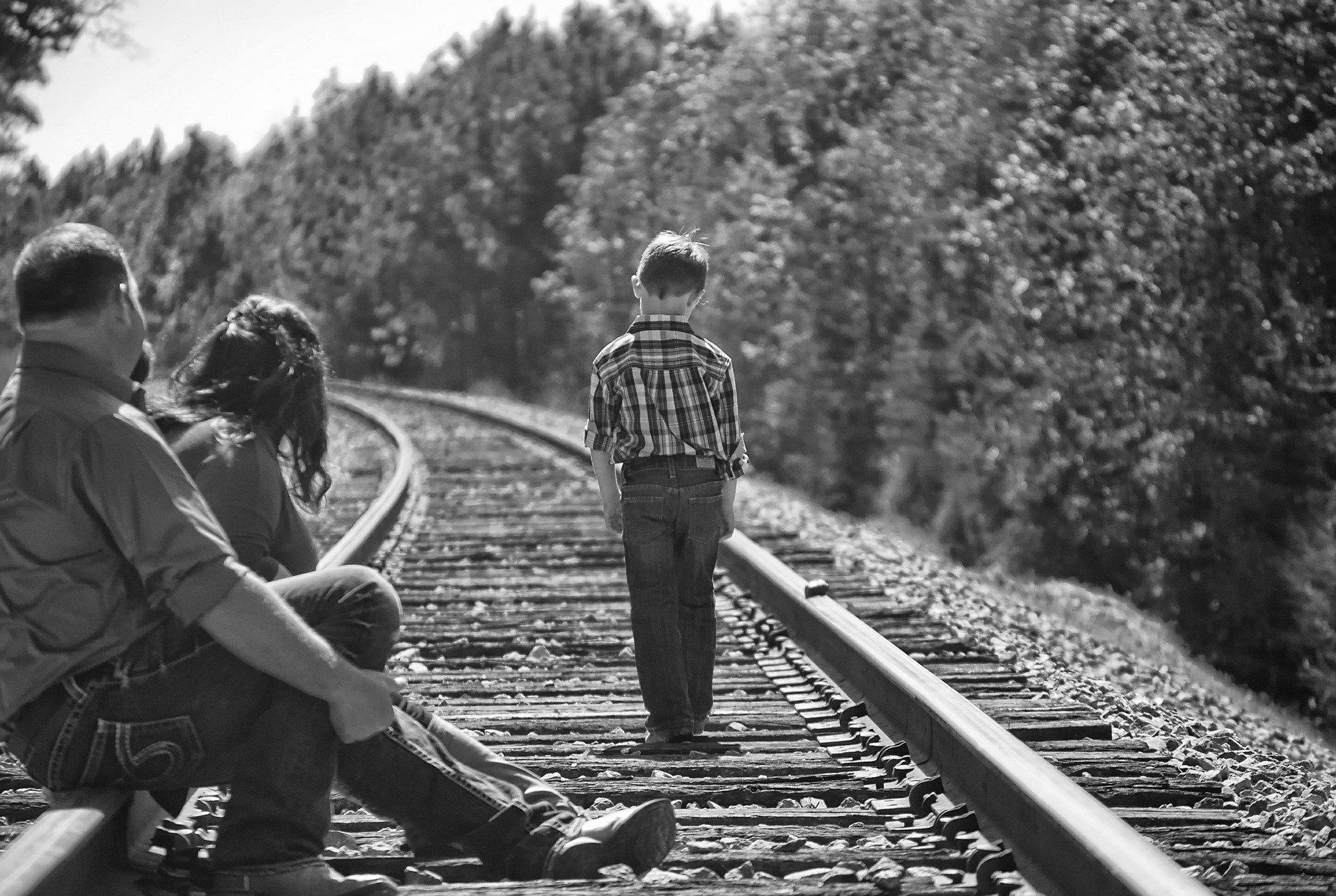un bambino cammina sui binari di un treno, mentre un uomo e una donna lo guardano allontanarsi seduti sui medesimi binari