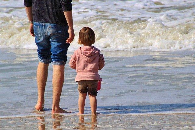 padre e figlia si godono un momento di spontaneità in riva al mare