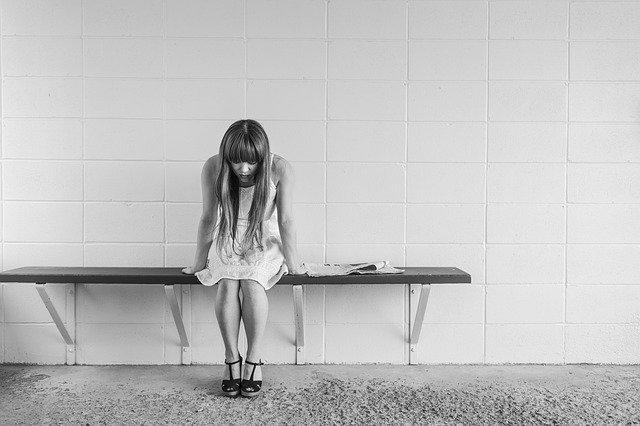 una donna seduta si mostra stanza e preoccupata