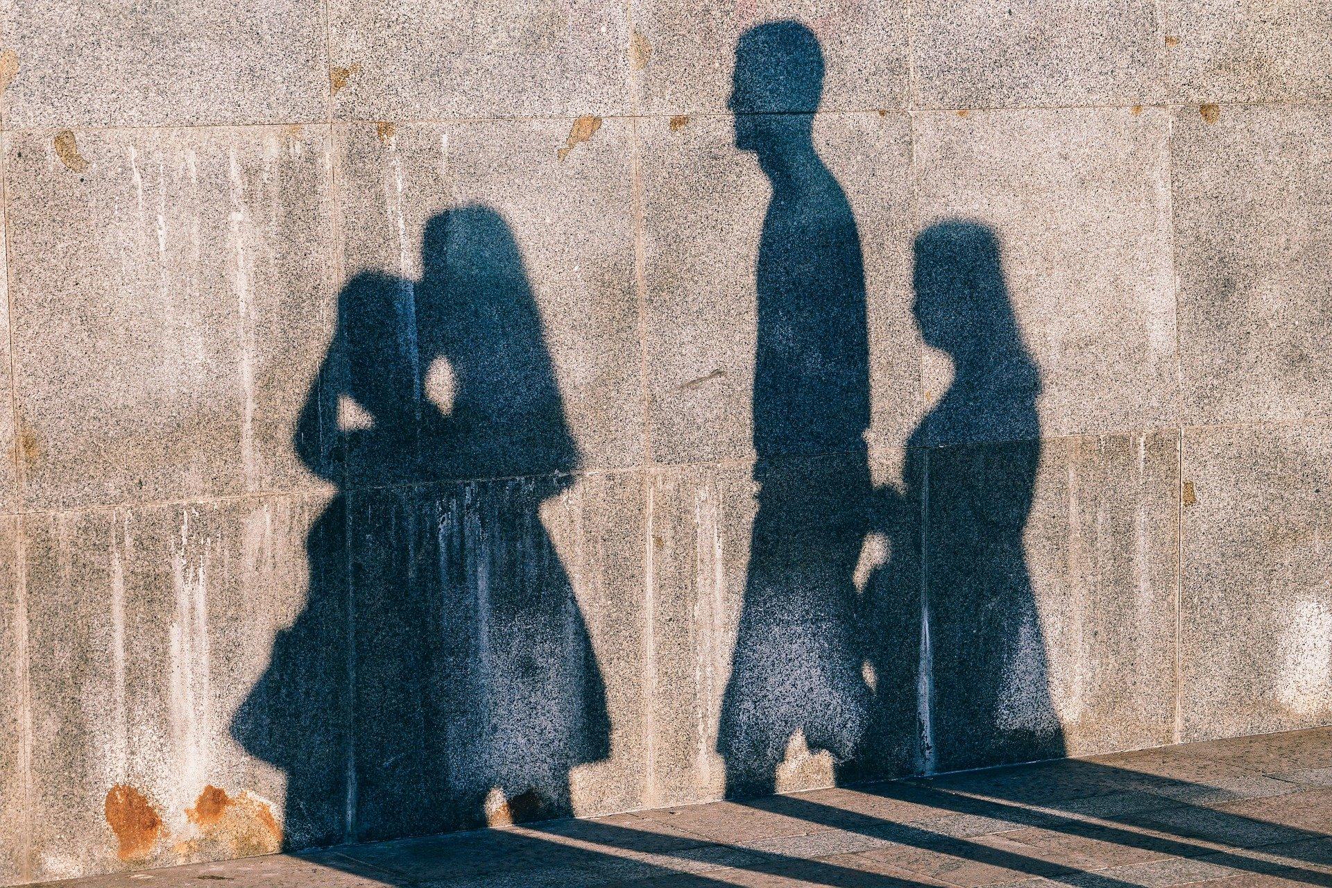muro in blocchi di cemento sul quale si riflettono ombre di quattro persone