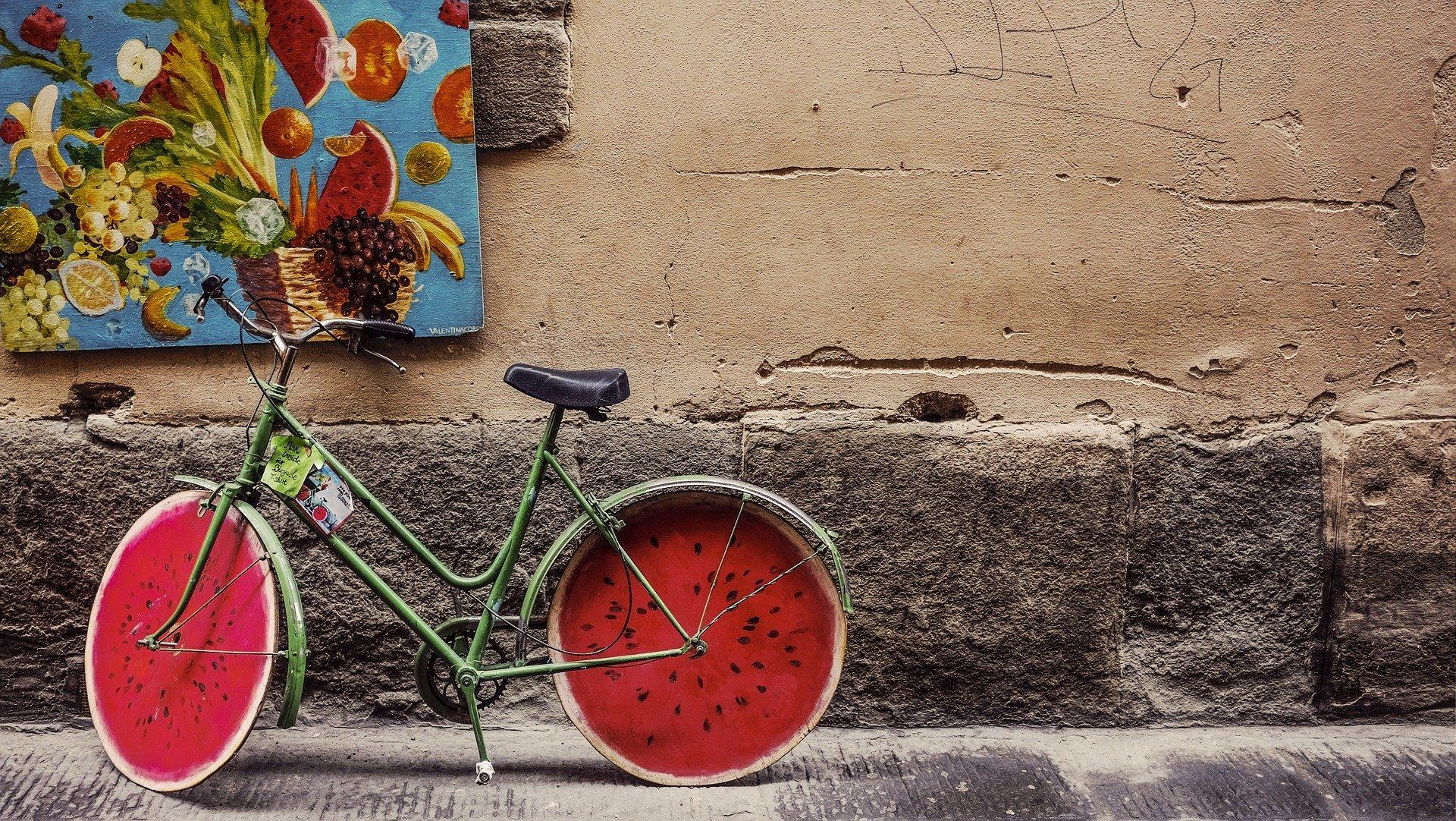 bicicletta con rote colorate a fetta di anguria, sotto un dipinto di frutta