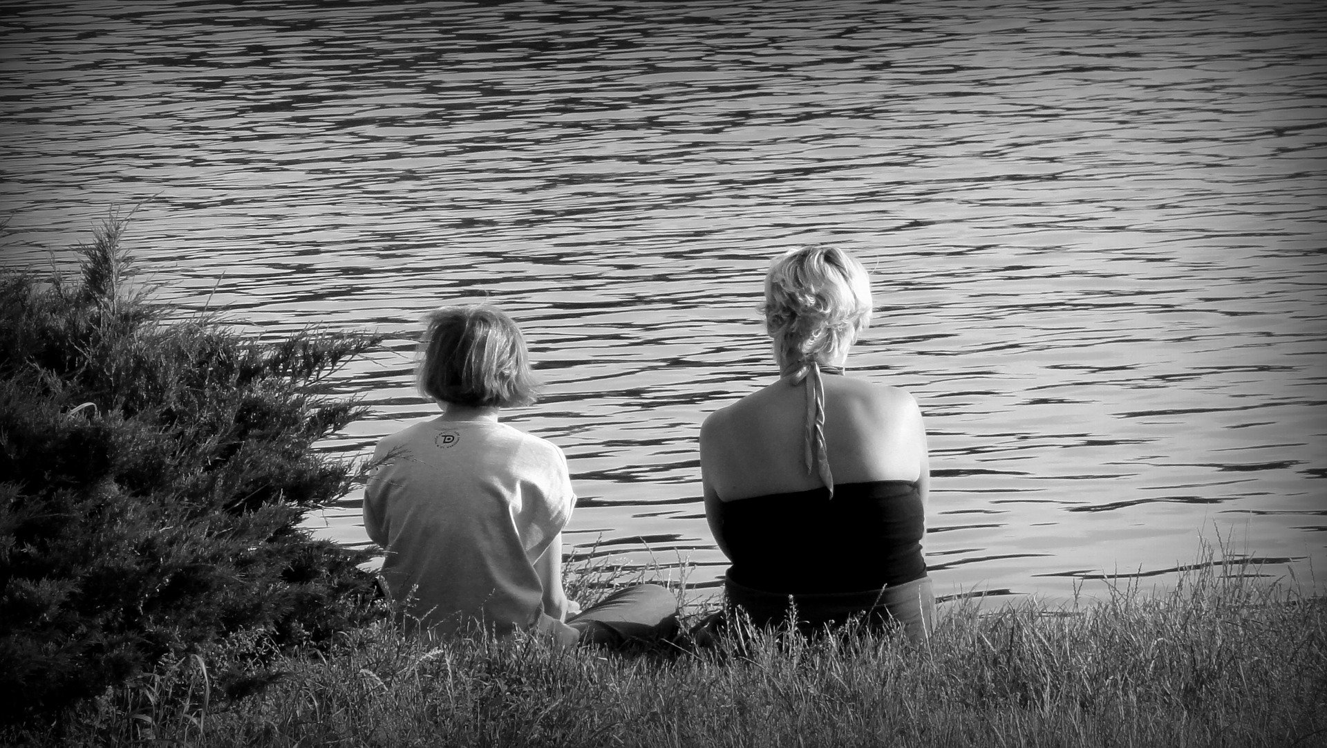 madre e figlio di spalle, seduti in riva ad un lago, foto in bianco e nero