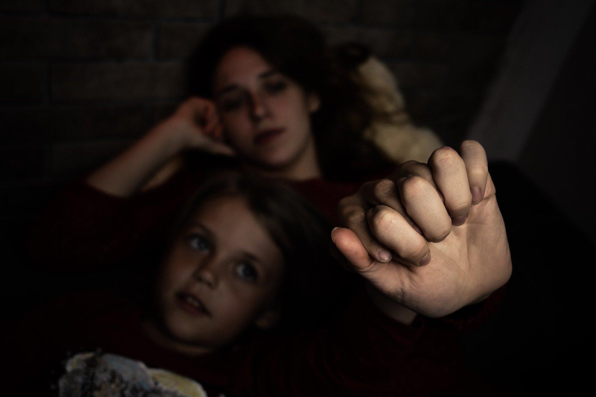 madre e figlio che si tengono per mano, in penombra