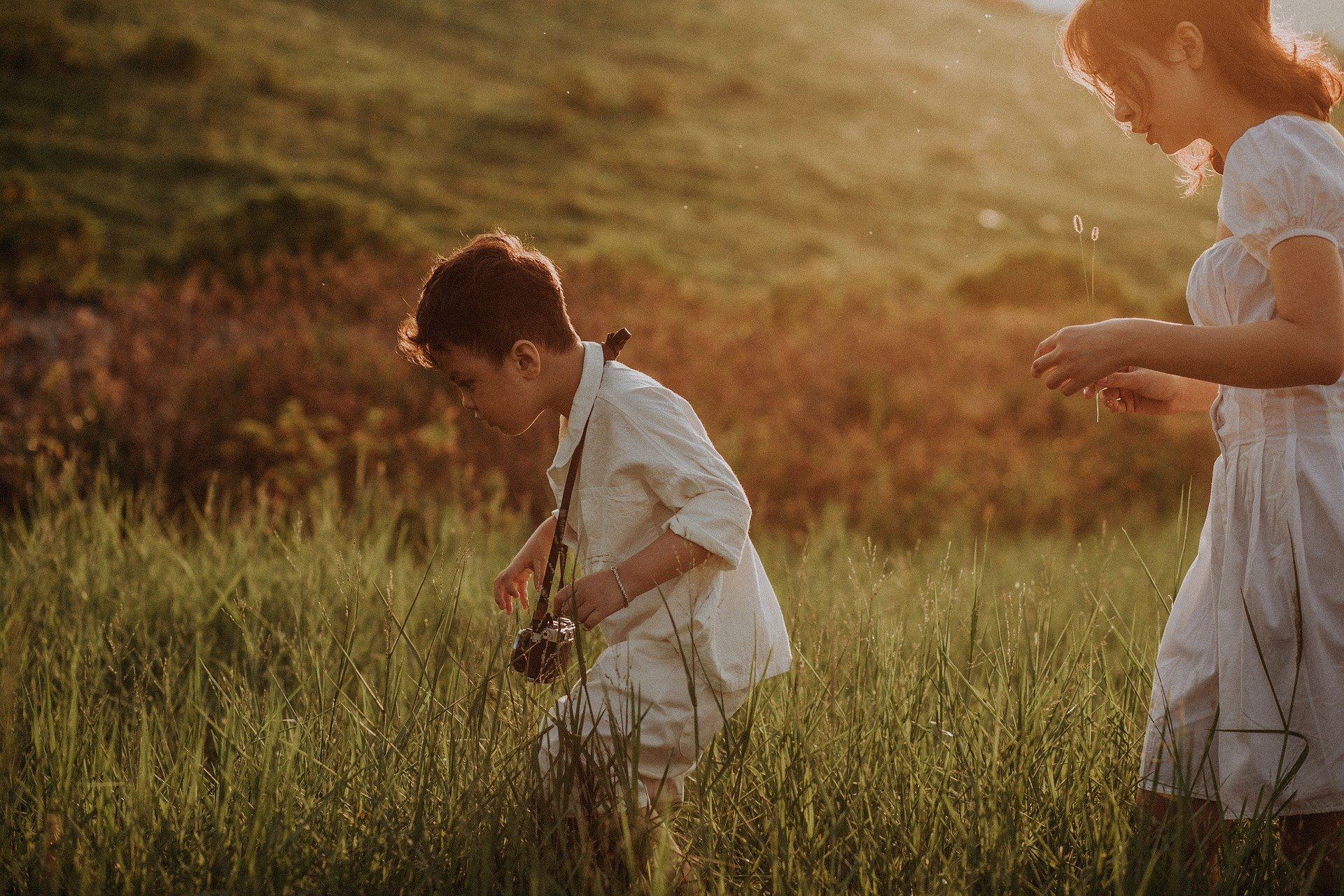 madre e figlio in un campo intenti ad osservare qualcosa nel prato