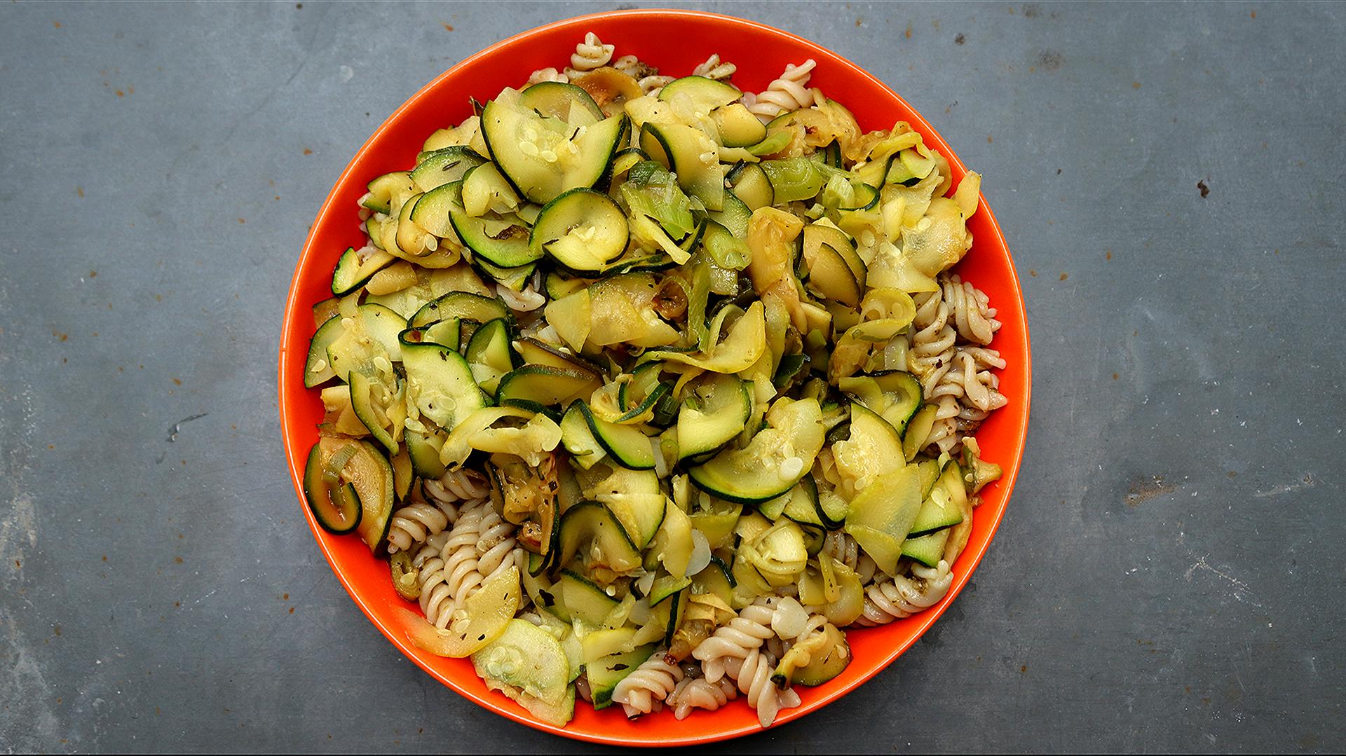 piatto di pasta rosso condito con zucchine marinate