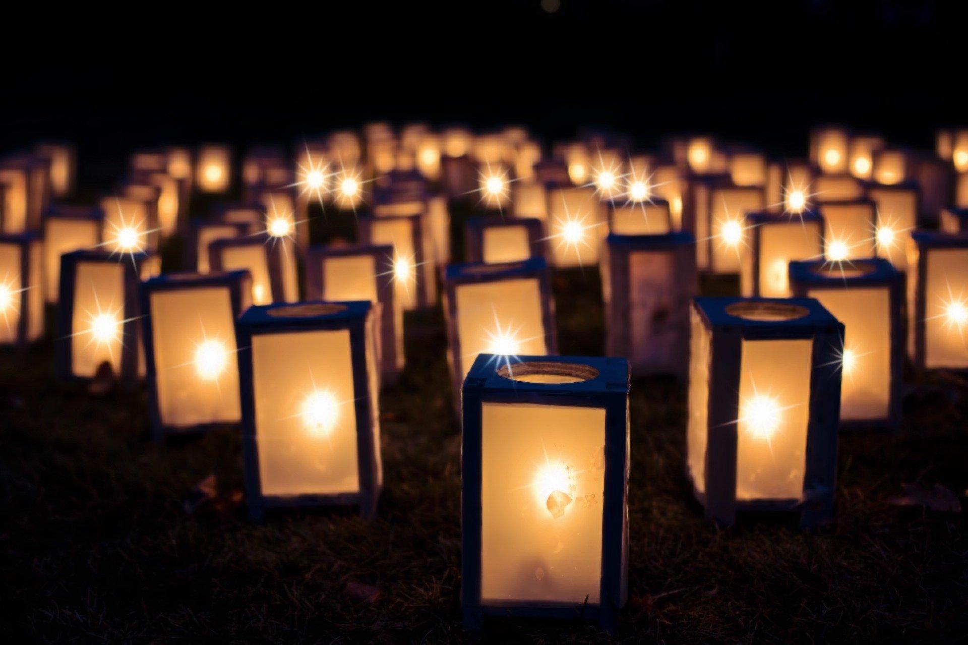 una moltitudine di lanterne accese per terra