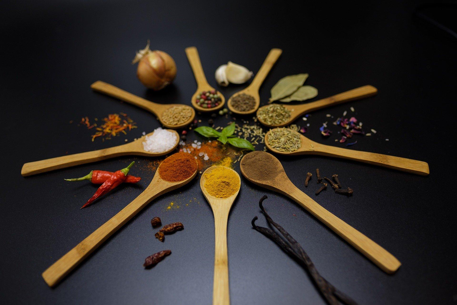 9 cucchiai di legno disposti a raggiera, ognuno contenente una spezia
