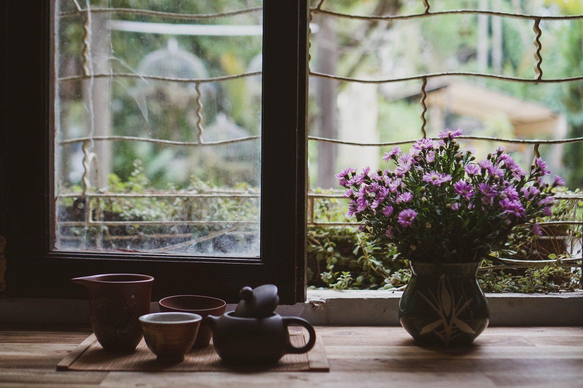 su un tavolo davanti ad una finestra, tazze di the e un vaso con un mazzo di fiori viola