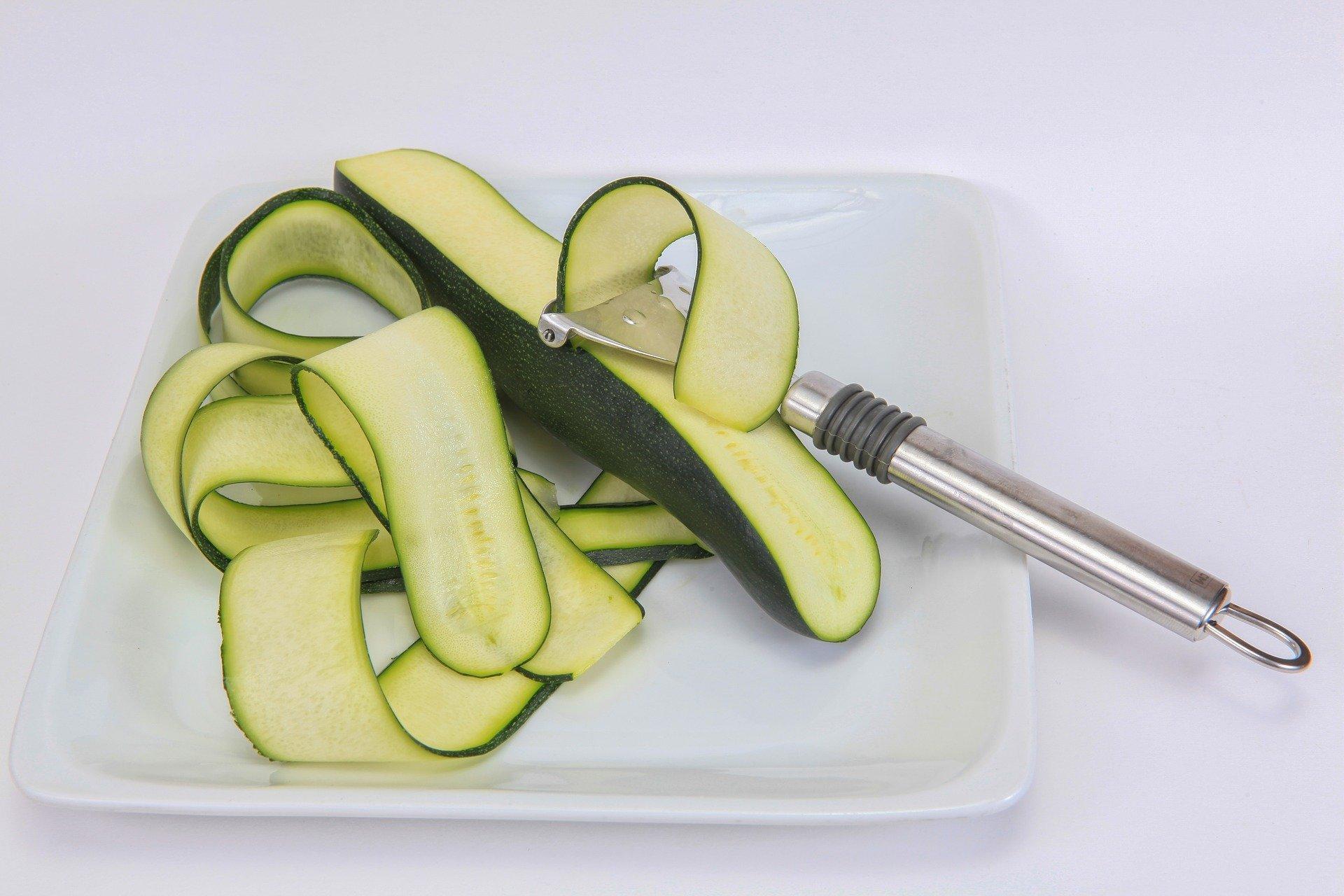 zucchine crude tagliate in lunghezza su un piatto con affettaverdure
