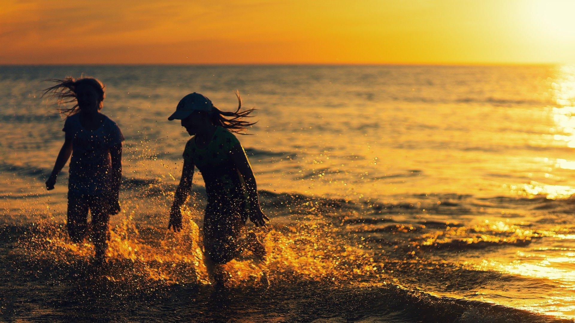 due ragazzine in ombra che si corrono dietro sul bagnasciuta al tramonto