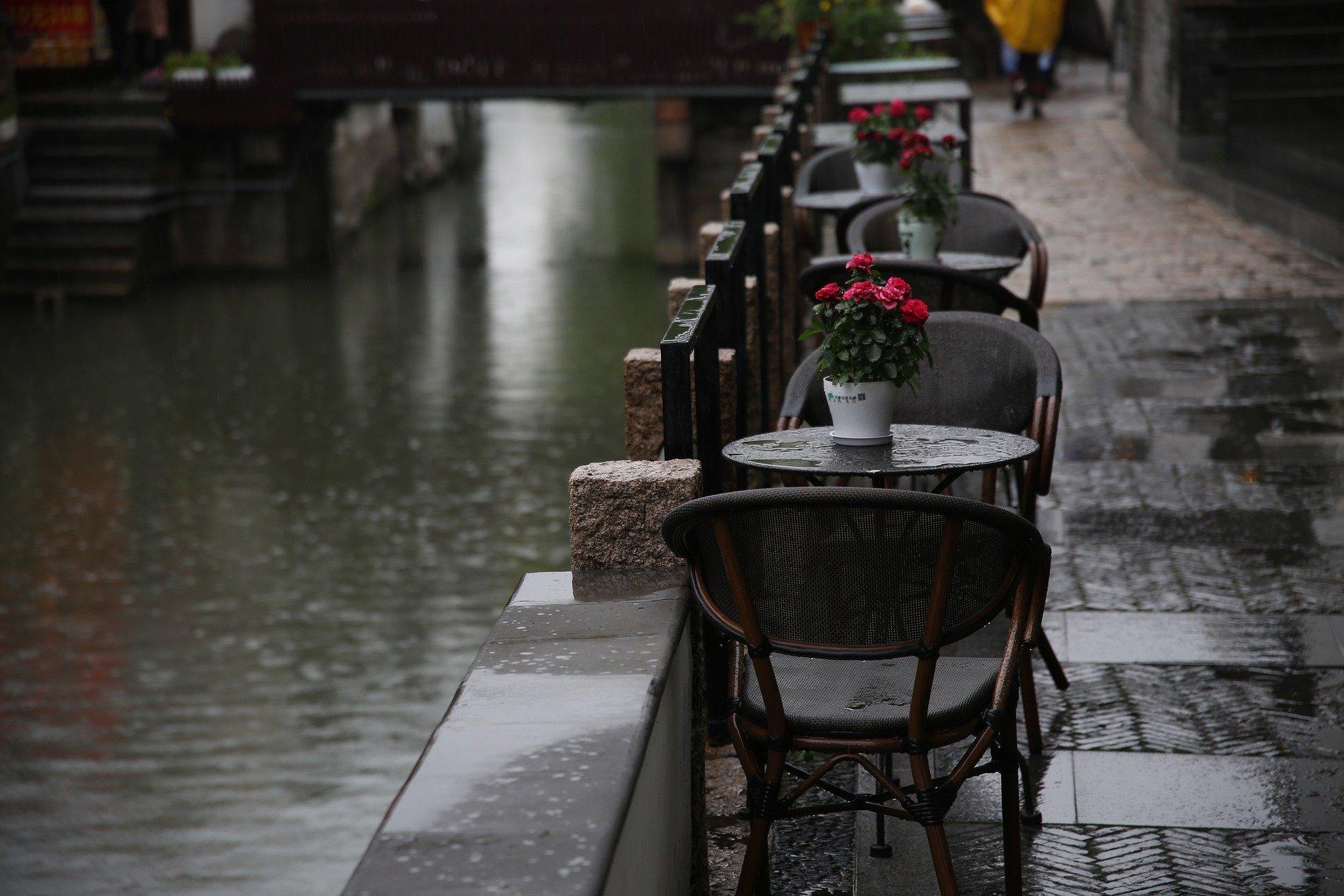 tavolini di un bar all'aperto lungo la strada, sotto la pioggia, con sopra un vaso di fiori rossi