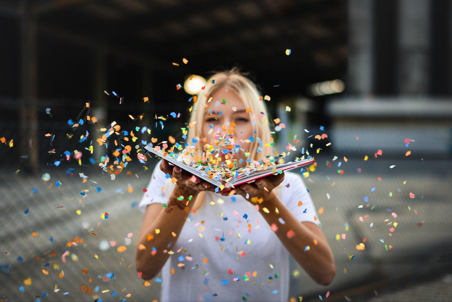 una donna con in mano un libro aperto, sul quale sta soffiando e dal quale stanno volando tanti coriandoli colorati